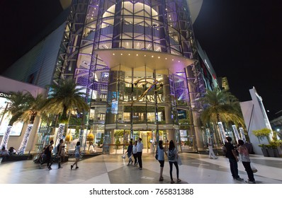 Outdoor panoramic scenic view in front of an entrance of Siam Paragon, one of the largest shopping center in Bangkok, Thailand at night in November 7  2017 . People walk back and forth