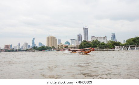 Outdoor panoramic scenic view of numerous skyscrapers nearby bank of Chao Phraya river in downtown of Bangkok, Thailand under environmental grayish cloudy sky in rainy season. Vintage motorboat moves.