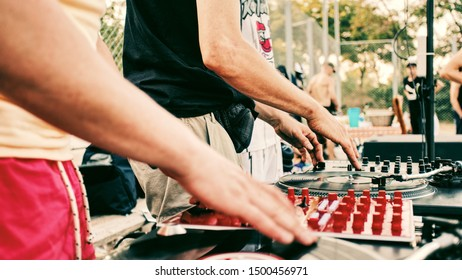 Outdoor party. Two Djs spinning vinyl record and turning mixer's controllers