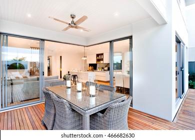 Patio exterior con mesa colocada al lado de la entrada de una casa moderna con cocina, hay velas en la mesa debajo del ventilador