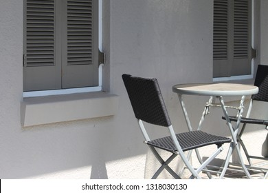 Outdoor patio furniture set, a small table and two folding chairs on a verandah in the sunshine and shade. The windows of the victorian house have grey closed shutters. And tessellated tile floor
