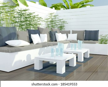 Outdoor patio seating area with big white and black sofa and two tables.