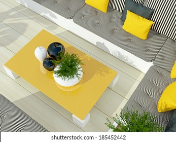 Outdoor patio seating area with big sofa and yellow table.