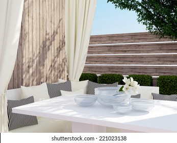 Outdoor patio seating area with big sofa, black and white pillows and table.
