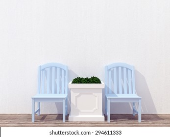 Outdoor patio seating area with blue wooden furniture, white wall.