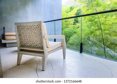 Outdoor patio seating area with wooden chair and garden outside view