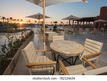 Outdoor patio terrace area with table set up and parasol umbrellas at tropical luxury hotel resort sunrise