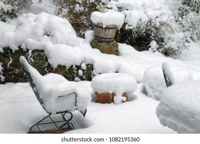 An outdoor patio winter wonderland, with furniture, planters, pots and garden vegetation heavily covered by deep snow in winter