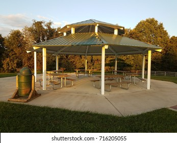 an outdoor pavillion with picnic tables, grill, and trash can