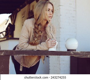 Outdoor photo of beautiful blond woman with long hair and perfect makeup wearing knitted sweater and scarf and posing at autumn park