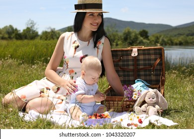 outdoor photo of beautiful family: mother with dark hair in elegant dress posing with her little cute baby boy in spring blossom garden