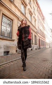 Outdoor photo of fashionable female model walking around city in winter vacation. Fashionable girl walking on Warsaw street in Old Town.