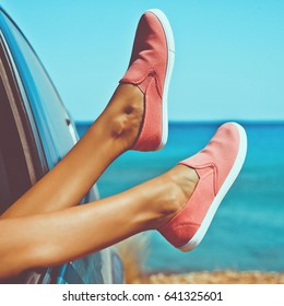 Outdoor photo of female legs from the window of car. Freedom, summer travel and road trip