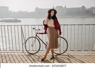 Outdoor photo of good-looking dark-haired girl in skirt spending time near river. Full-length portrait of wonderful caucasian lady with bicycle.