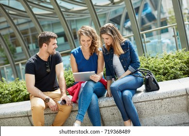Outdoor photo of happy friends using tablet on the street.
