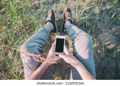 Outdoor photo of man sitting on grass holding phone with blank screen. Concept of being in contact every moment in a day
