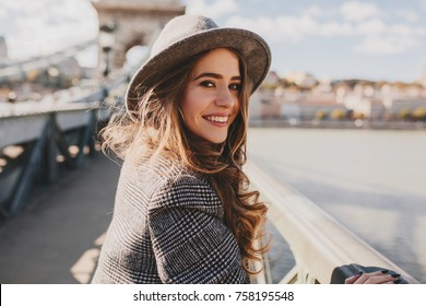 Outdoor photo of romantic european woman with curly hairstyle spending time outdoor, exploring european city. Graceful young lady in gray coat and hat enjoying views on embankment.