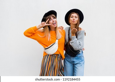 Outdoor photo of two cheerful female friends spending great time together , posing on white background. Autumn concept. Space for text.