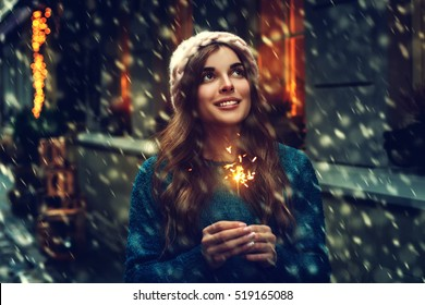 Outdoor photo of young beautiful happy smiling girl holding sparkler, walking on street. Model looking up, wearing stylish winter clothes. Waist up. Christmas, New Year, concept. Magic snowfall. Toned
