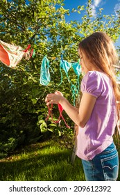 Outdoor photo of young girl drying clothes on clothesline