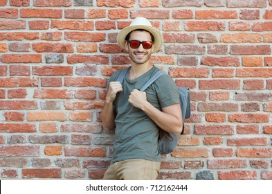 Outdoor photo of young hipster guy standing against wall of red bricks with gray backpack, wearing casual neutral clothes, sunhat and trendy sunglasses, looking at street waiting for city adventures