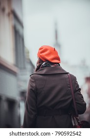 Outdoor photo of young woman with brown hair walking through the streets of Lille, France