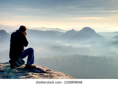 Outdoor photographer with tripod and camera on rock thinking. Thick fog in autumnal countryside. Man work on sharp clif.