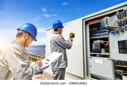 In an outdoor photovoltaic area, engineers are checking the amount of photovoltaic power generation