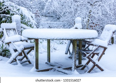 Outdoor picnic table and chairs covered in a thick layer of  untouched deep snow