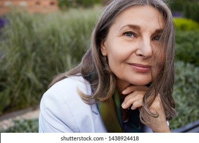Outdoor picture of beautiful mature woman with wise blue eyes enjoying her retirement, sitting in park with flowers in background. Beauty, nature, elderly people, age and lifestyle concept