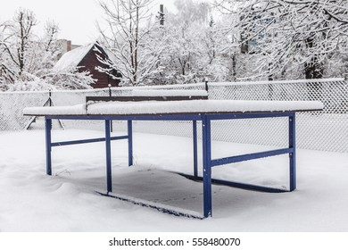 Outdoor ping-pong table covered with snow in winter