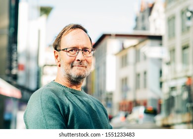 Outdoor portrait of 50 - 55 year old man wearing green pullover and eyeglasses