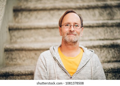 Outdoor portrait of 50 year old man wearing grey hoody and eyeglasses