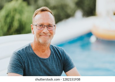 Outdoor portrait of 50 year old man resting by the pool, wearing blue t-shirt and glasses