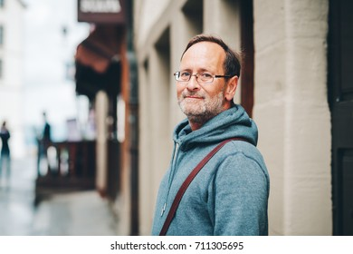 Outdoor portrait of 50 year old man wearing blue hoody and eyeglasses