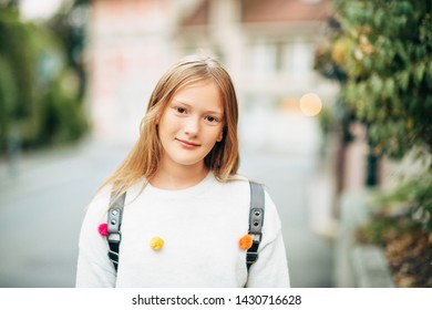 Outdoor portrait of adorable 10-12 year old girl wearing backpack