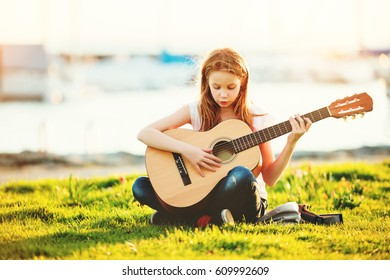 Outdoor portrait of adorable 9 year old kid girl playing guitar outdoors, sitting on bright green lawn at warm summer sunset
