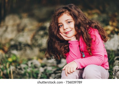 Outdoor portrait of adorable little 3-4 year old girl with beautiful long hair, wearing pink fleece jacket