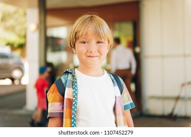 Outdoor portrait of adorable little boy ready to go back to school, wearing colorful shirt and backpack