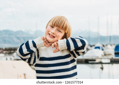 Outdoor portrait of adorable little boy with blond hair, wearing stripe marine pullover, playing by the lake on a nice day