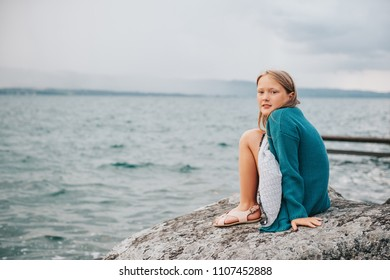 Outdoor portrait of adorable little girl playing next to lake, wearing white dress and green cardigan jacket