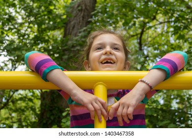 Outdoor portrait of adorable little girl playing in a park with a big toothless smile.