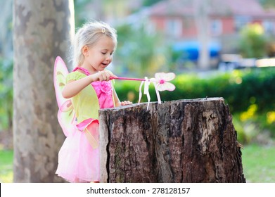 An outdoor portrait of adorable little girl in a fairy costume or outfit holding a magic wand
