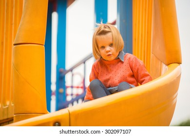 Outdoor portrait of adorable little girl playing in summer park