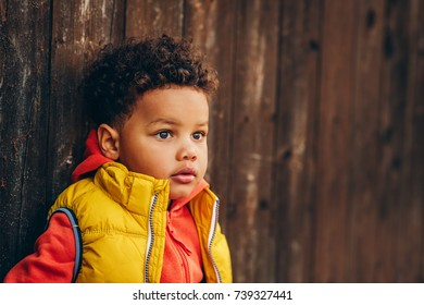 Outdoor portrait of adorable toddler boy posing outside against brown wooden background, wearing orange hoody jacket any bright yellow vest coat