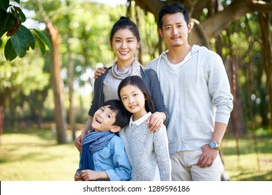 outdoor portrait of an asian family with two children.