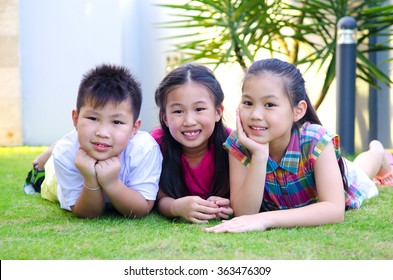 Outdoor portrait of asian kids lying on the grass