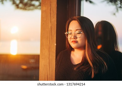 Outdoor portrait of asian plus size model at sunset, wearing eyeglasses