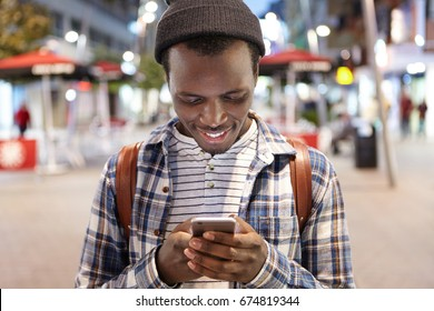 Outdoor portrait of attractive male with dark skin carrying rucksack wearing black hat and shirt reading interesting post online via social networks using free internet being in big city or metropolis