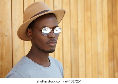 Outdoor portrait of attractive trendy-looking young Afro American man with faint smile wearing stylish sunglasses, hat and t-shirt, hiding from hot summer sun in shadow at wooden wall. Horizontal